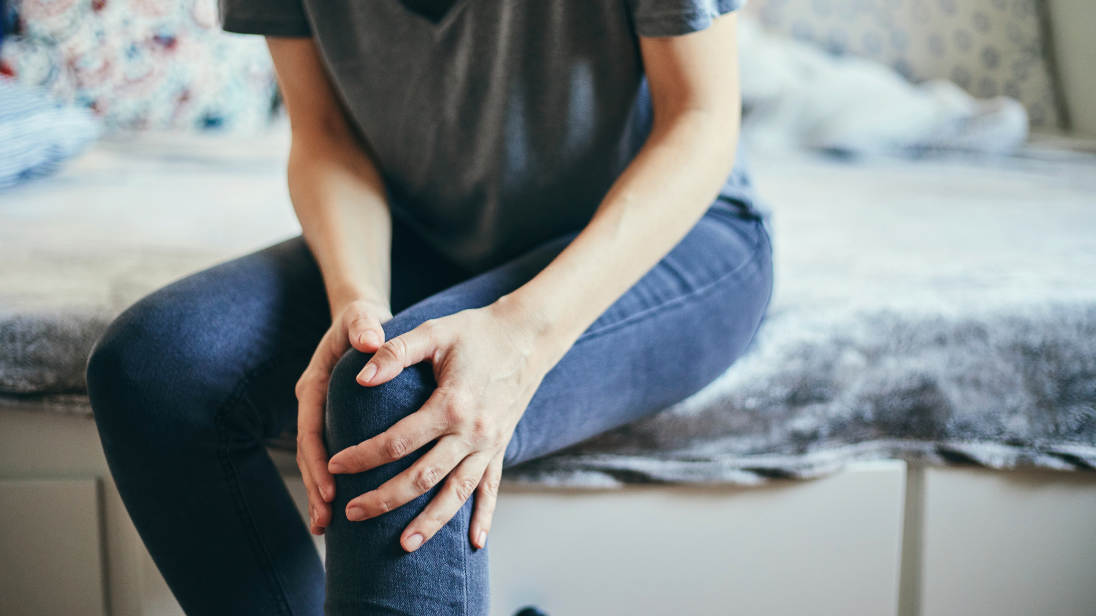 person clutching knee in pain