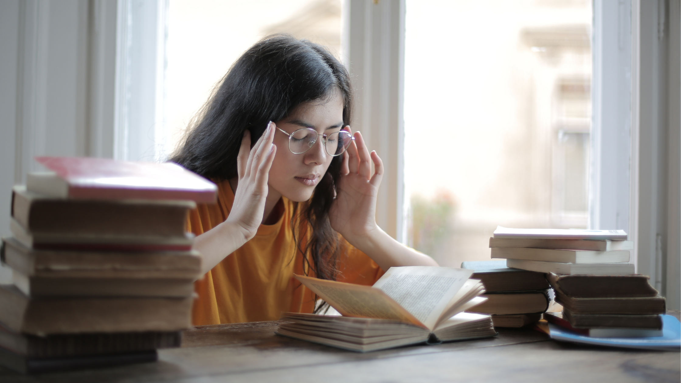 woman reading book applying pressure on her temples